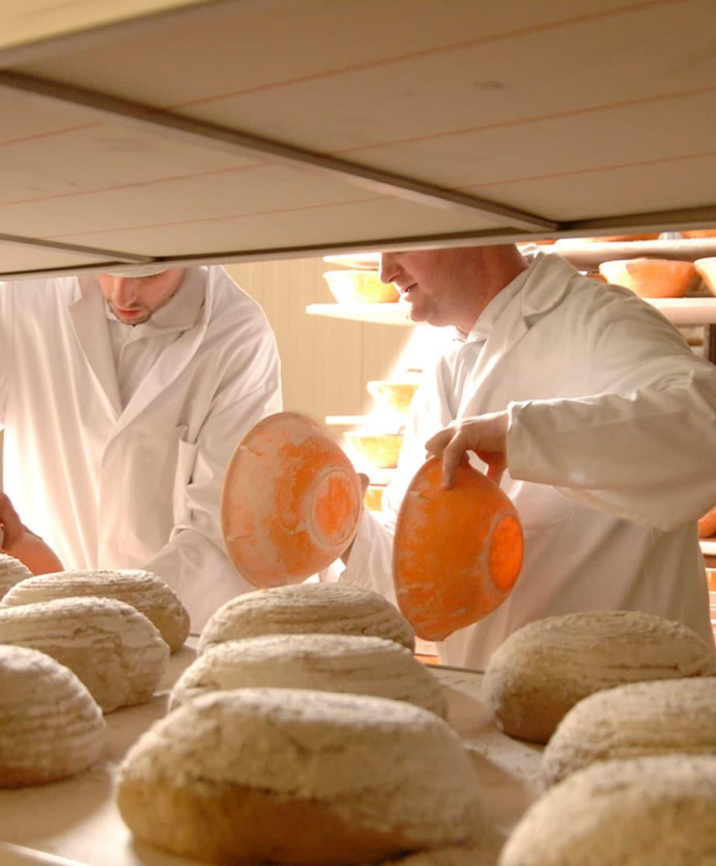 Bäcker schiebt Brote in den Ofen