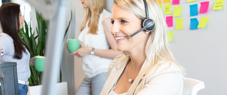 Frau spricht übers Headset mit einem Kunden
